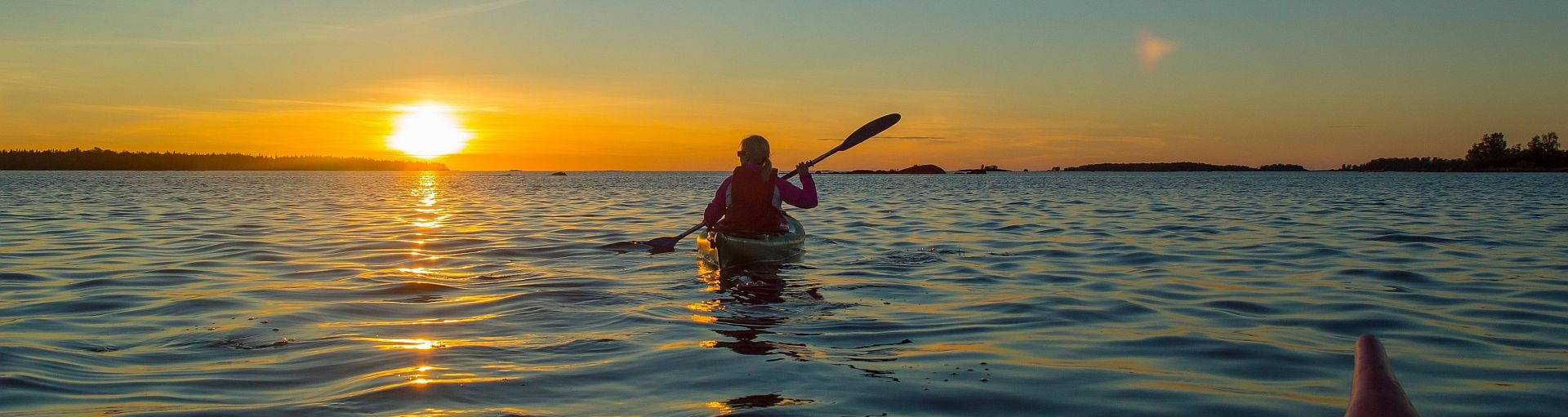 person paddling while the sun sets
