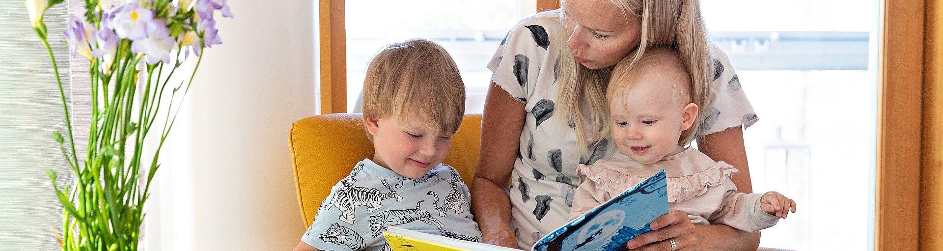 Äiti lukee kirjaa lasten kanssa